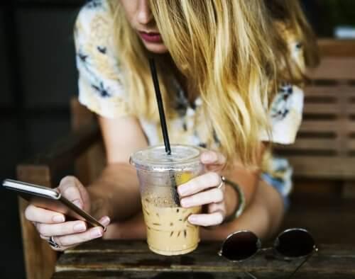 En kvinne på telefonen mens hun drikker is-kaffe.