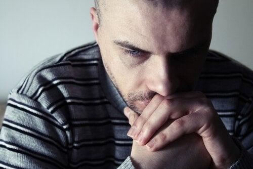 En trist mann ser ned på gulvet.