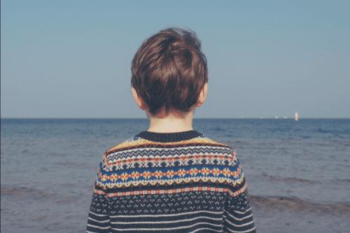 Et sørgende barn som ser ut til havet.