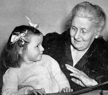 Maria Montessori snakker med en liten jente.