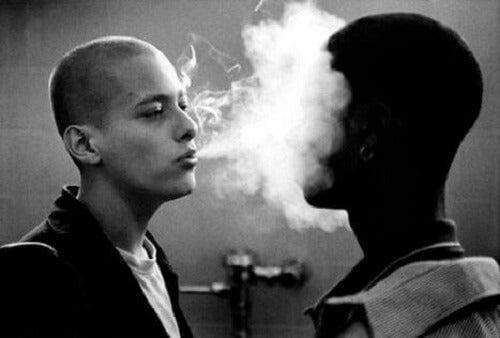 Hvit mann blåser røyk i ansiktet på svart mann.
