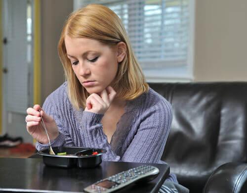 Jente med depresjon som spiser.