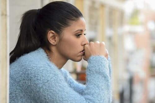 Tankefull kvinne sitter med ansiktet lent mot knyttede hender. Hun ser ut som om noe bekymrer eller plager henne.