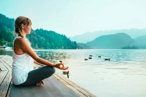Ung kvinne mediterer på en brygge ved en innsjø