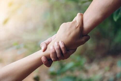 Vi ser bildet av to hender som holder hverandre. Et bilde på vennskap