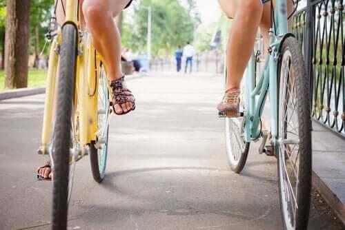 Vi ser benene på to venner syker side ved side på hver sin sykkel