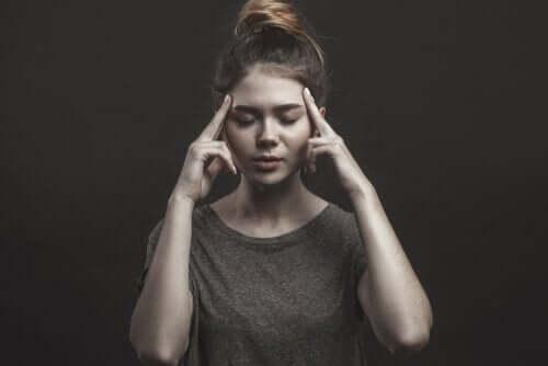 En kvinne tenker med lukkede øyne.