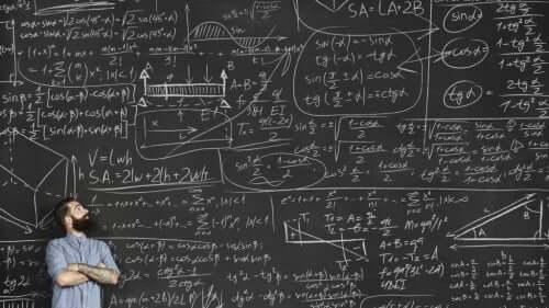 En mann foran en tavle full av formler.