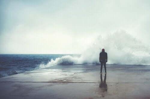 Mann som ser på bølgene.
