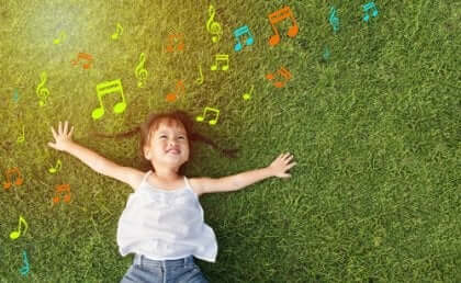 Glad jente ligger i gresset og lytter til musikk