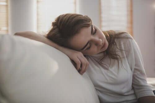 Utmattet kvinne med energistjelende vaner