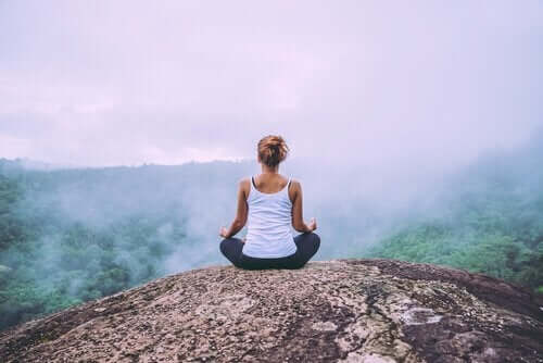 Kvinne mediterer i naturen