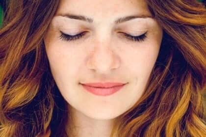 Kvinne smiler med lukkede øyne