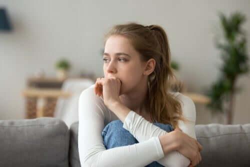 En kvinne som sitter i sofaen med knærne i brystet, ser gjennomtenkt eller bekymret ut.
