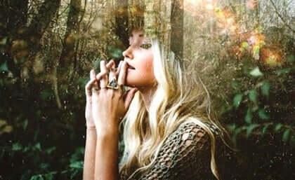 En kvinne som sitter i skogen og tenker.