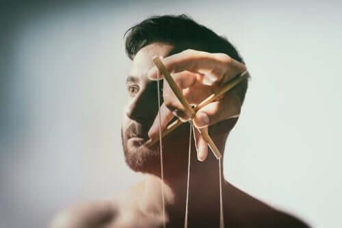 Marionette strenger foran ansiktet til en mann, som viser at hjernevasking er ekte.