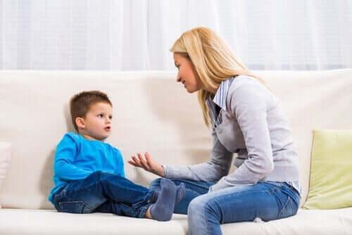 En mamma som sitter i sofaen sammen med sønnen sin og forklarte ham noe.