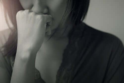 En person som holder hånden under nesen, i tankene.