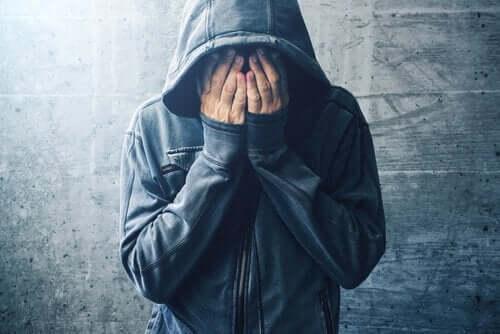Mann med hette dekker ansiktet med hendene