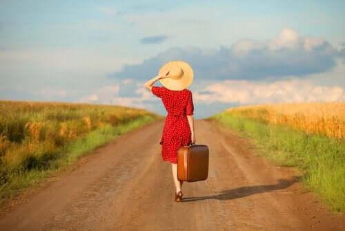 En kvinne med en koffert som går nedover veien.
