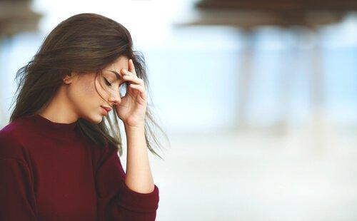 En kvinne med hånden i ansiktet, som vil styrke selvkontrollen.