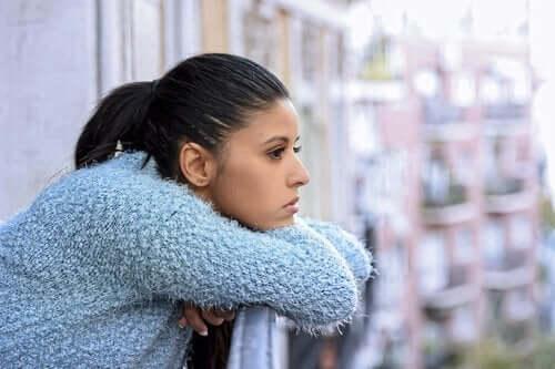 En kvinne som lener seg på balkongen sin i dype tanker.