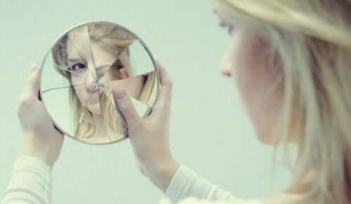 En kvinne som ser på seg selv i et ødelagt speil.
