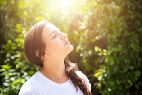 Et bilde som viser en kvinne som ser opp med lukkede øyne og tar inn naturen rundt seg.