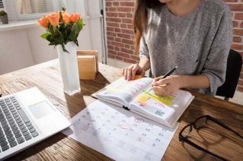 Hvordan styrke viljestyrken din: En kvinne som sitter ved et skrivebord.