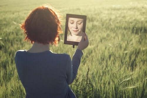 En rødhåret kvinne holder opp et speil forran sitt eget ansikt samtidig som hun lukker øynene.