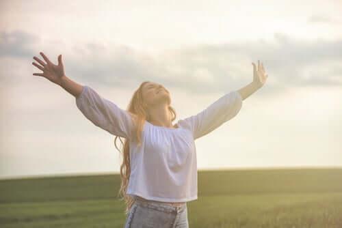 Lykkelig kvinne på åker strekker armene opp i luften