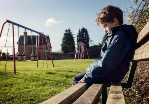 Barn sitter alene på en benk på en lekeplass