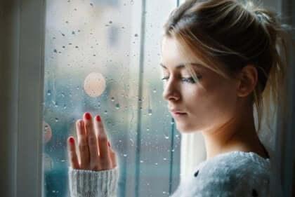 Trist kvinne med hånden på et vindu