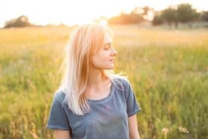 Kvinne med lukkede øyne står i en eng