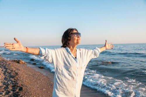 En eldre kvinne som står på en strand med armene spredt bredt.