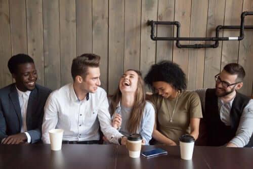 En gruppe venner og lojale mennesker som ler sammen ved et bord.