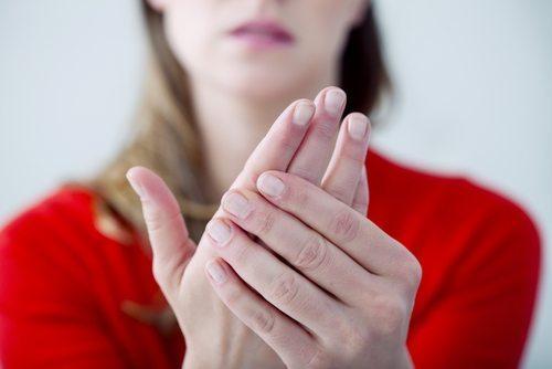 En kvinne som holder hånden sin i smerter.