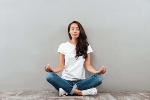 En kvinne som mediterer på gulvet.