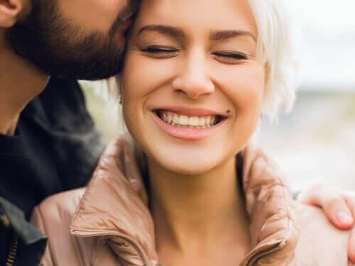 En mann som kysser partneren sin på pannen.