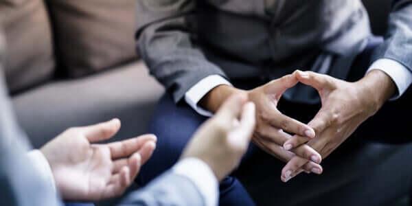 Bildet av to menns hender under en samtale
