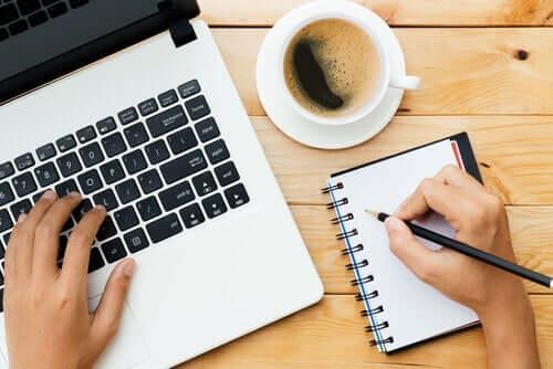 Noen skriver i en dagbok ved siden av sin bærbare datamaskin.