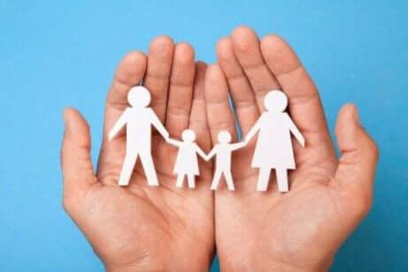 hender som holder et papirutklipp av en familie