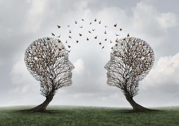 Bildet av to trær som ser ut som hoder med fugler som flyr mellom dem