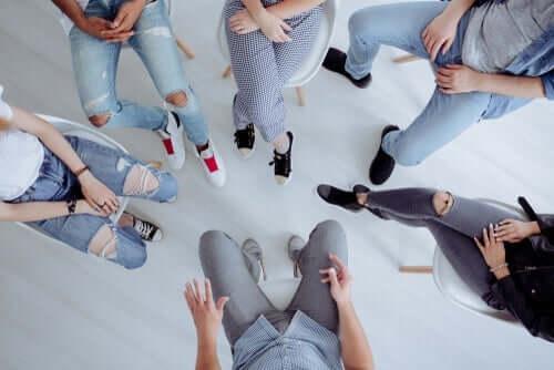 En gruppe ungdommer sitter samlet i en ring. Vi ser bare deres ben og overkropper.