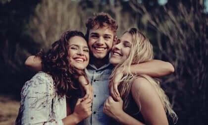 Tre venner som klemmer.