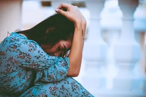 Kvinne i en blå, lang kjole skjuler ansiktet i hendene.