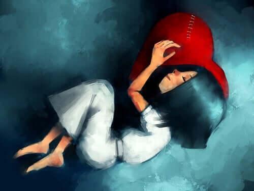 En jente sover med hodet på en rød pute formet som et hjerte