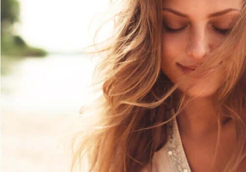 Kvinne som smiler med øynene lukket