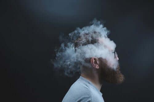 Hodet på en skjeggete mann er omringet av røykskyer