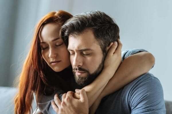 En rødhåret ung kvinne og en mørkhåret mann omfavner hverandre